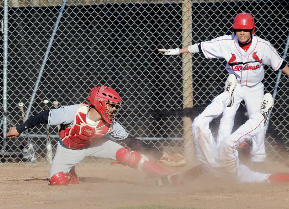 As teammate Ryota Fujikara, background, signals safe, Patrick Santini of Greenwich scores in the bottom of the 5th inning as Fairfield Warde catcher Anthony Miller is late with the tag during the boys high school baseball game between Greenwich High School and Fairfield Warde High School at Greenwich, Friday, April 5, 2013. Photo: Bob Luckey / Greenwich Time