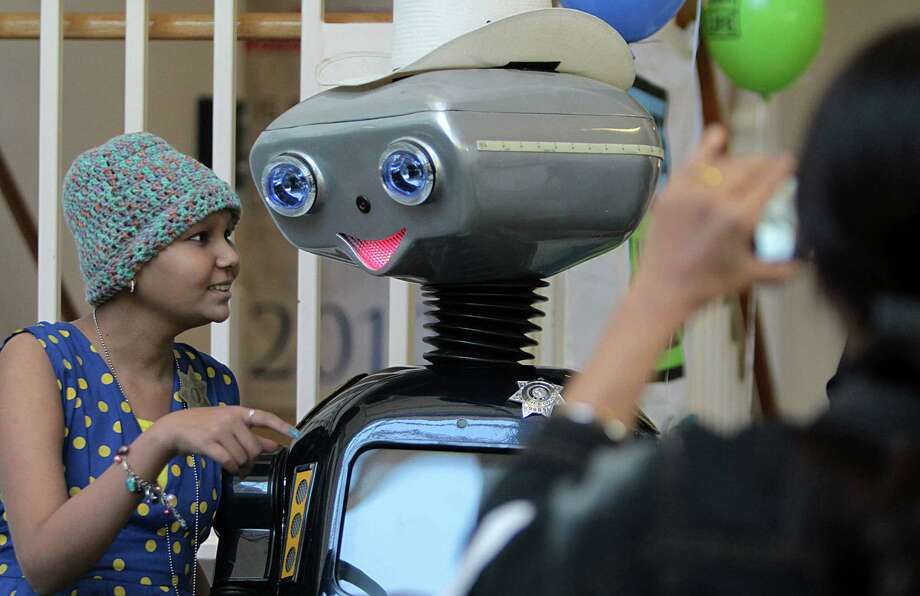 """Rakshanda Jain, of India, tells """"GISMO"""" the Safety Robot, to turn around for a photo after she and her family were served lunch. Harris County Sheriff's Office served lunch to the children and families waiting for organ transplants and living at the Ronald McDonald House in honor of National Donate Life Month. Photo: Mayra Beltran, Houston Chronicle / © 2013 Houston Chronicle"""