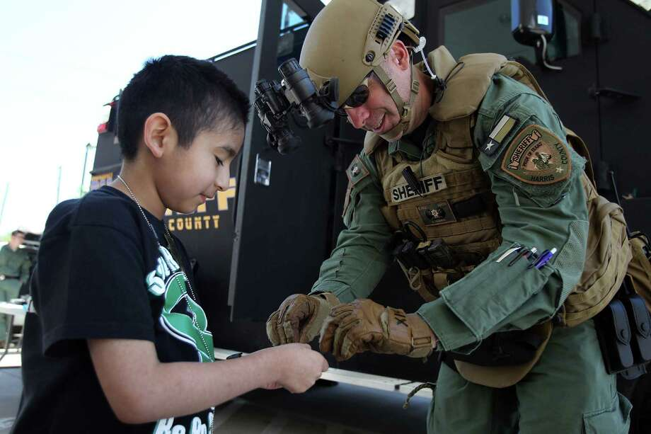 Andrew Alcala, 8, receives a toy soldier from Harris County Sheriffs Office Deputy B. Brawner, of the High Risk Operation Unit, while parked outside the Ronald McDonald House on Friday, April 5, 2013, in Houston. Photo: Mayra Beltran, Houston Chronicle / © 2013 Houston Chronicle