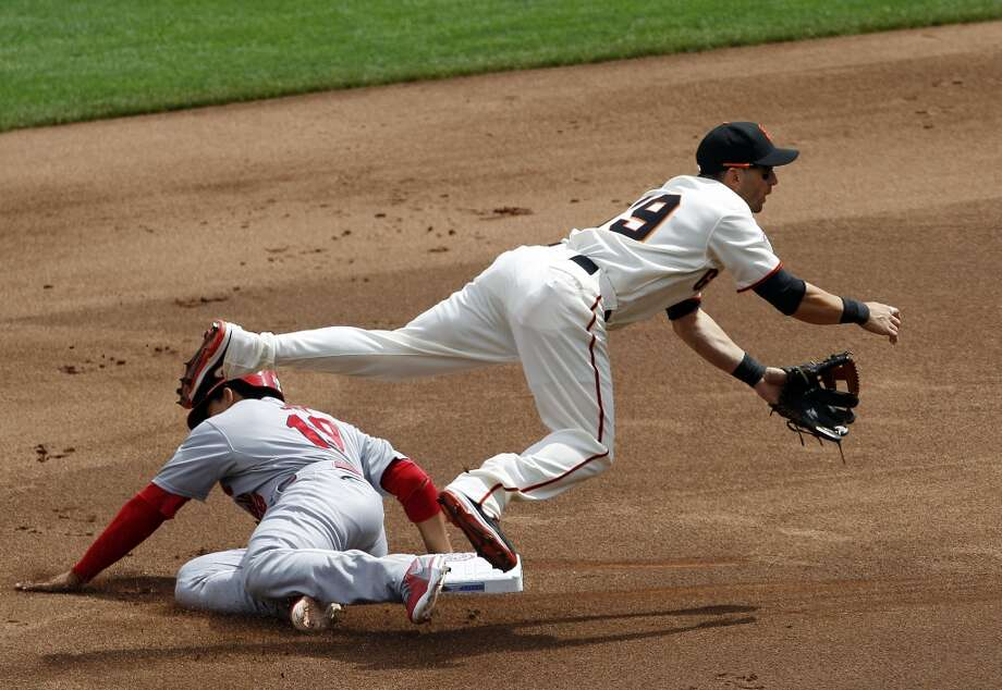 Giants second baseman Marco Scutaro is upended by Cardinals\' Jon Jay as he completes a double play in the first inning. The San Francisco Giants played the St. Louis Cardinals in their 2013 home opener at AT&T Park in San Francisco, Calif., on Friday, April 5, 2013. Photo: Carlos Avila Gonzalez, The Chronicle / ONLINE_YES