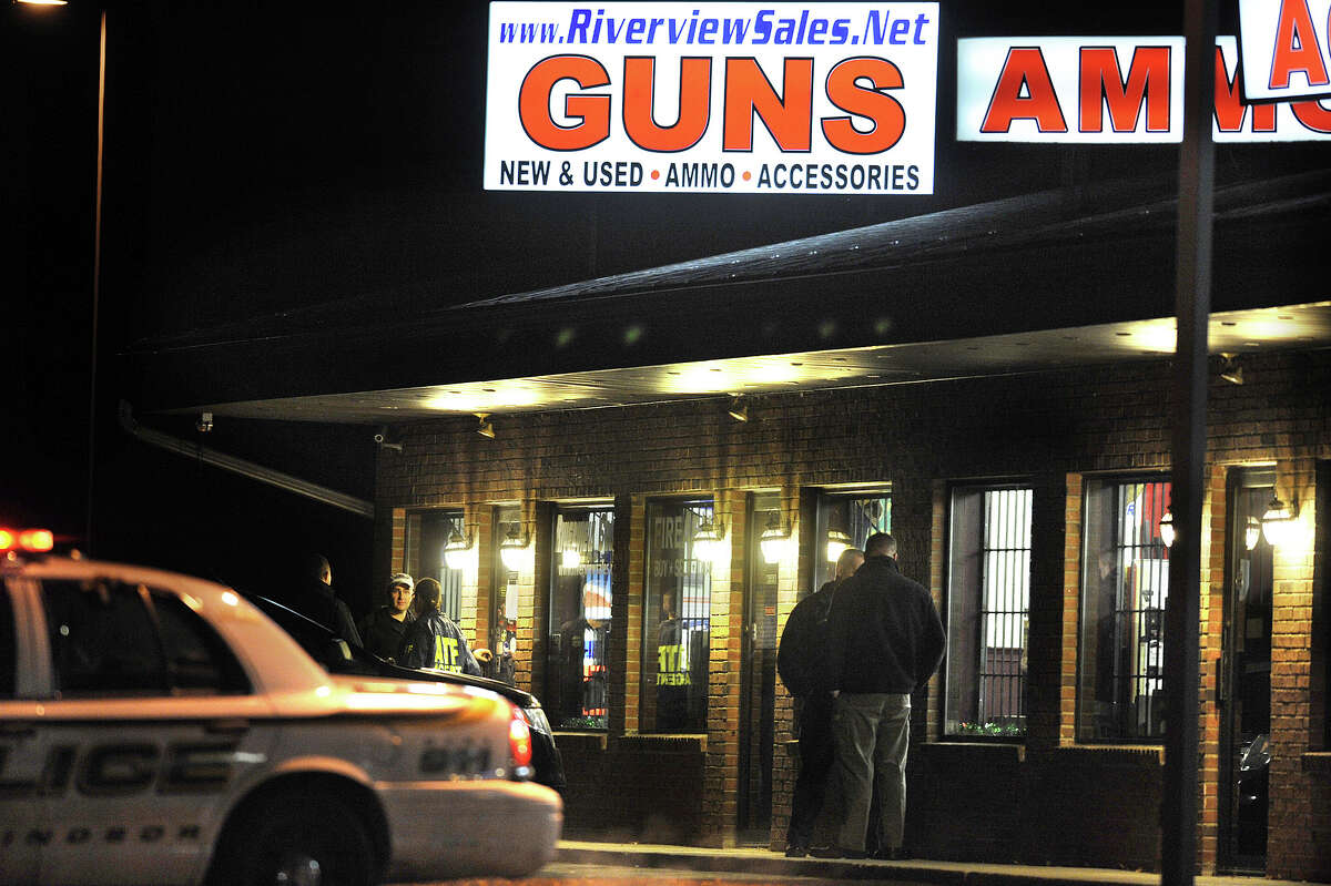 In this Dec. 20, 2012 photo, law enforcement officials stand outside Riverview Gun Sales, as authorities raid the store in East Windsor, Conn. The shop, which sold a gun to Nancy Lanza, mother of Newtown school shooter Adam Lanza, had its federal firearms license revoked by the Bureau of Alcohol, Tobacco, Firearms and Explosives. (AP Photo/Jessica Hill)