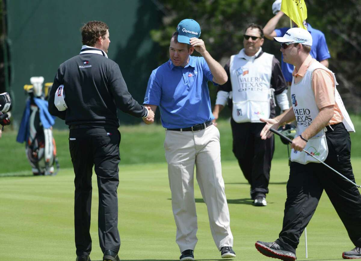 D.J. Trahan, left, and Troy Matteson shake hands after their second-round finishes a the Valero Texas Open at TPC San Antonio's AT&T Oaks Course on Friday, April 5, 2013.