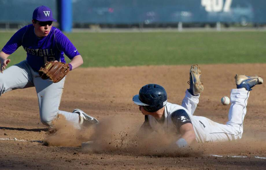 Brett Phillips of Wilton slides safely into third base as Westhill's Peter Horn looks for the ball during Friday's baseball game at Wilton High School on April 5, 2013. Photo: Lindsay Perry / Stamford Advocate