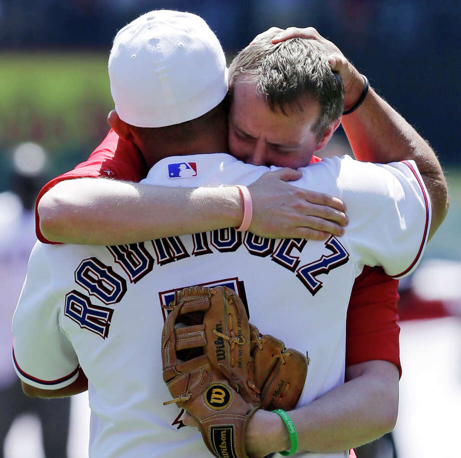 Robbie Parker, right, receives a hug from Texas Rangers representative Ivan Rodriguez after throwing out the ceremonial first pitch before a baseball game between the Los Angeles Angels and the Rangers, Friday April 5, 2013, in Arlington, Texas. Parker, a North Texas native whose 6-year-old daughter, Emilie, was among the victims of the Sandy Hook school shooting in Connecticut, threw out the first pitch before the Rangers' home-opener, their favorite team. Photo: Tony Gutierrez
