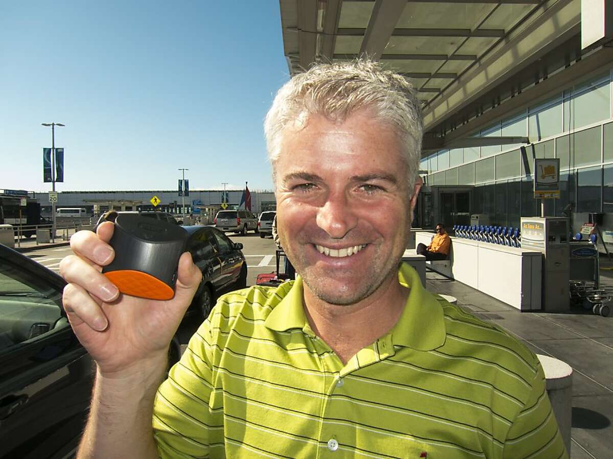 CEO John McGuire holds up the Game Golf device which tracks your golfing performance.