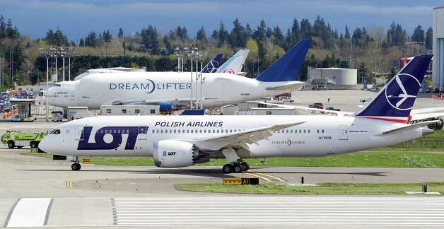EVERETT, WA - APRIL 05: A LOT Polish Airlines Boeing 787 Dreamliner taxis past a Boeing 747 Dreamlifter after a certification flight April 5, 2013 at Paine Field in Everett, Washington. The flight was the final certification test for the new battery system o