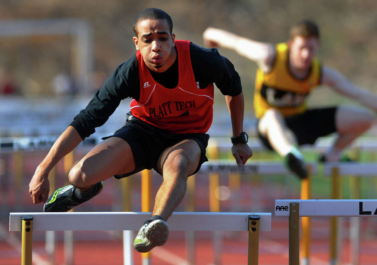 Platt Tech's Carlos Urena clears a hurdle, during boys and girls track meet action against Jonathan Law High in Milford, Conn. on Friday April 5, 2013.