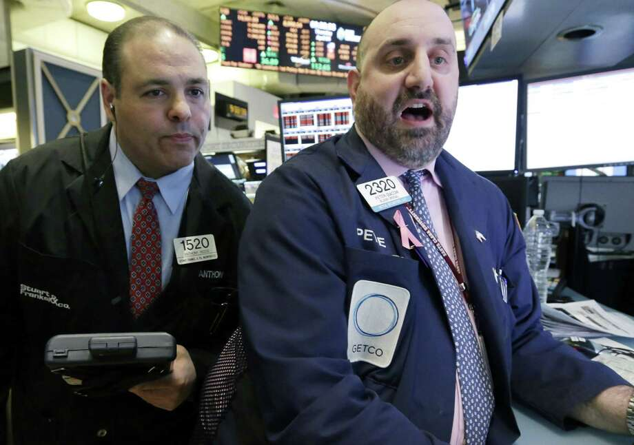 In this Thursday, April 4, 2013, photo, Trader Anthony Riccio, left, and specialist Peter Giacchi work on the floor of the New York Stock Exchange. Japan's benchmark stock index surged to its highest level in more than four years Friday April 5, 2013, its second straight day of big gains after the central bank announced aggressive action to lift the economy out of a prolonged slump. European stocks fell in early trading. (AP Photo/Richard Drew) Photo: Richard Drew