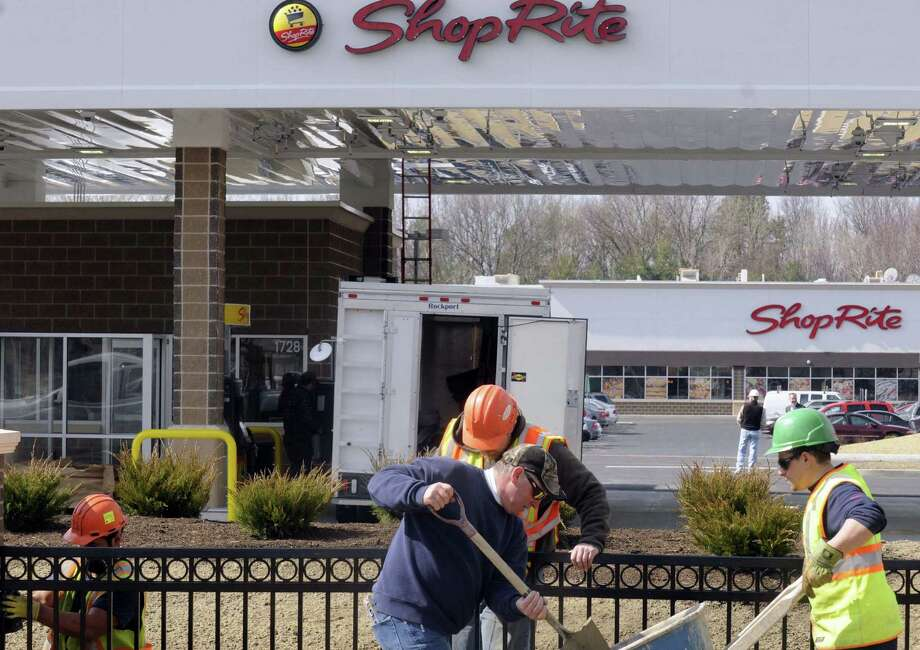 A crew from AFSCO Fence works on installing a fence in preparation for the ShopRite at 1730 central Avenue grand opening this Sunday on Friday April 5, 2013 in Colonie, N.Y. (Michael P. Farrell/Times Union) Photo: Michael P. Farrell