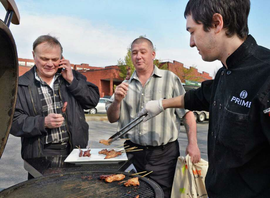 Mezzone Hospitality's Kelmy Tejeda, at right, serves up barbecue to Ian Davies left, and Jimmy Morton of Royal Fireside of Mendon, MA during the Northeast Agricultural Biomass Heating Seminar  outside the Saratoga Springs City Center Friday April 5, 2013.  (John Carl D'Annibale / Times Union) Photo: John Carl D'Annibale / 00021659A
