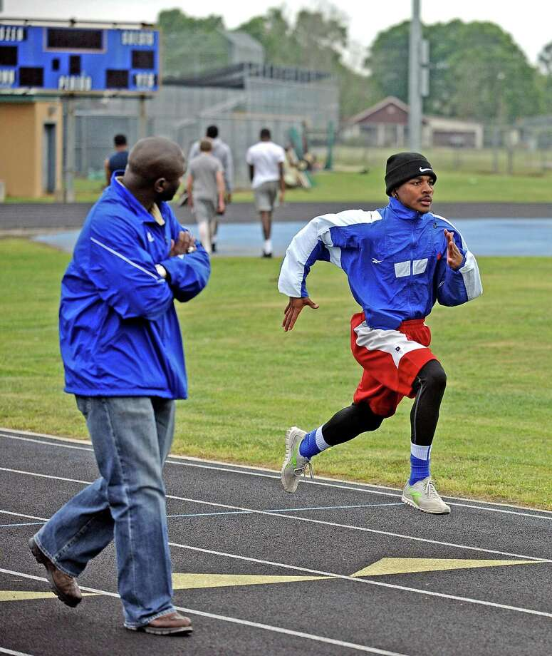 Ozen High School senior Jakobi Jones runs sprints as Coach Freddie Strange looks on during practice on Wednesday, March 3, 2013. Photo taken: Randy Edwards/The Enterprise