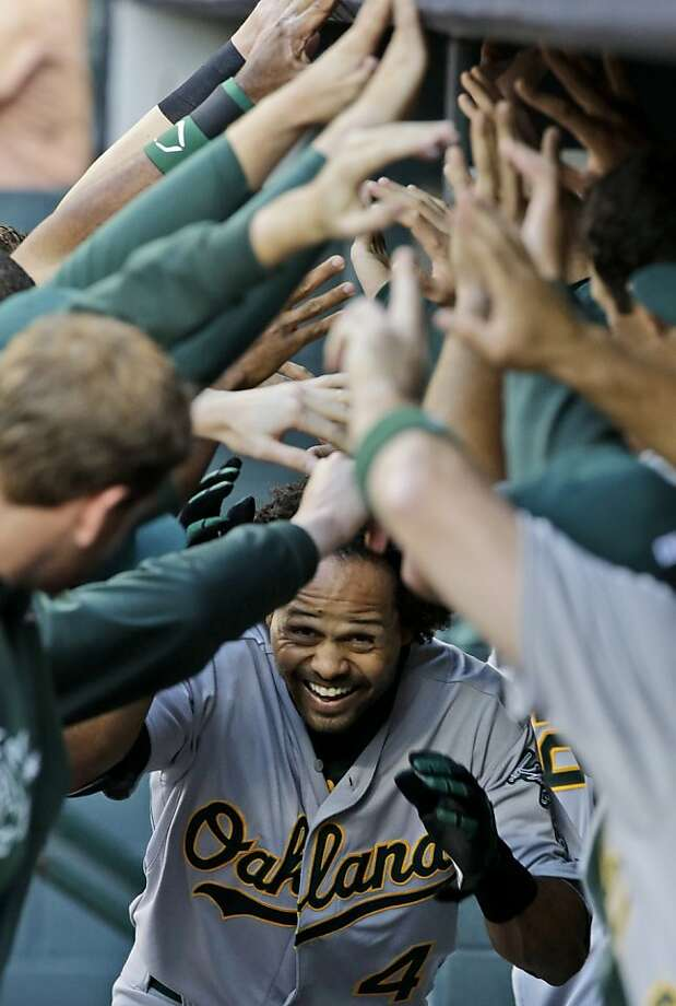 Oakland Athletics' Coco Crisp is welcomed back to the dugout after hitting a solo home run to start the baseball game against the Houston Astros, Friday, April 5, 2013, in Houston. (AP Photo/Pat Sullivan) Photo: Pat Sullivan, Associated Press