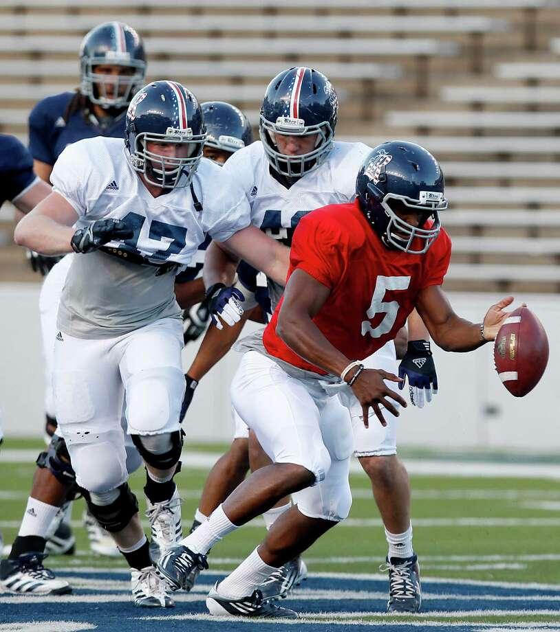 Rice quarterback Driphus Jackson fumbles the ball on a rush. Photo: Thomas B. Shea, For The Chronicle / © 2013 Thomas B. Shea