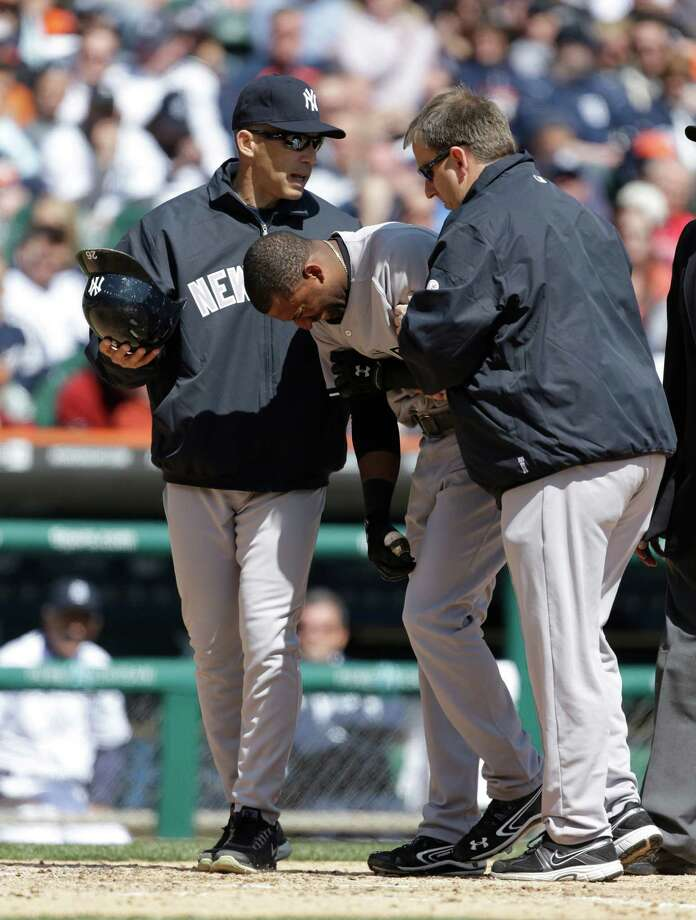 New York Yankees' Eduardo Nunez grimaces while helped to the dugout by manager Joe Girardi, left, and assistant trainer Mark Littlefield, after being hit by a pitch from Detroit Tigers starting pitcher Doug Fister during the fourth inning of a baseball game in Detroit, Friday, April 5, 2013. (AP Photo/Carlos Osorio) Photo: Carlos Osorio