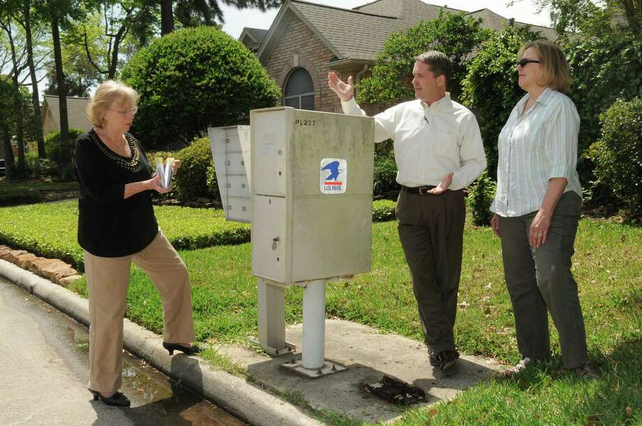 As their Kings Crossing neighbor Faith Hiller, left, picks up her mail, Jim Cooper and Joan Leon show where their mailbox unit was before it was removed because of disrepair.  Until the boxes are replaced, mail will be delivered directly to each resident's home. Photo: Jerry Baker, Freelance