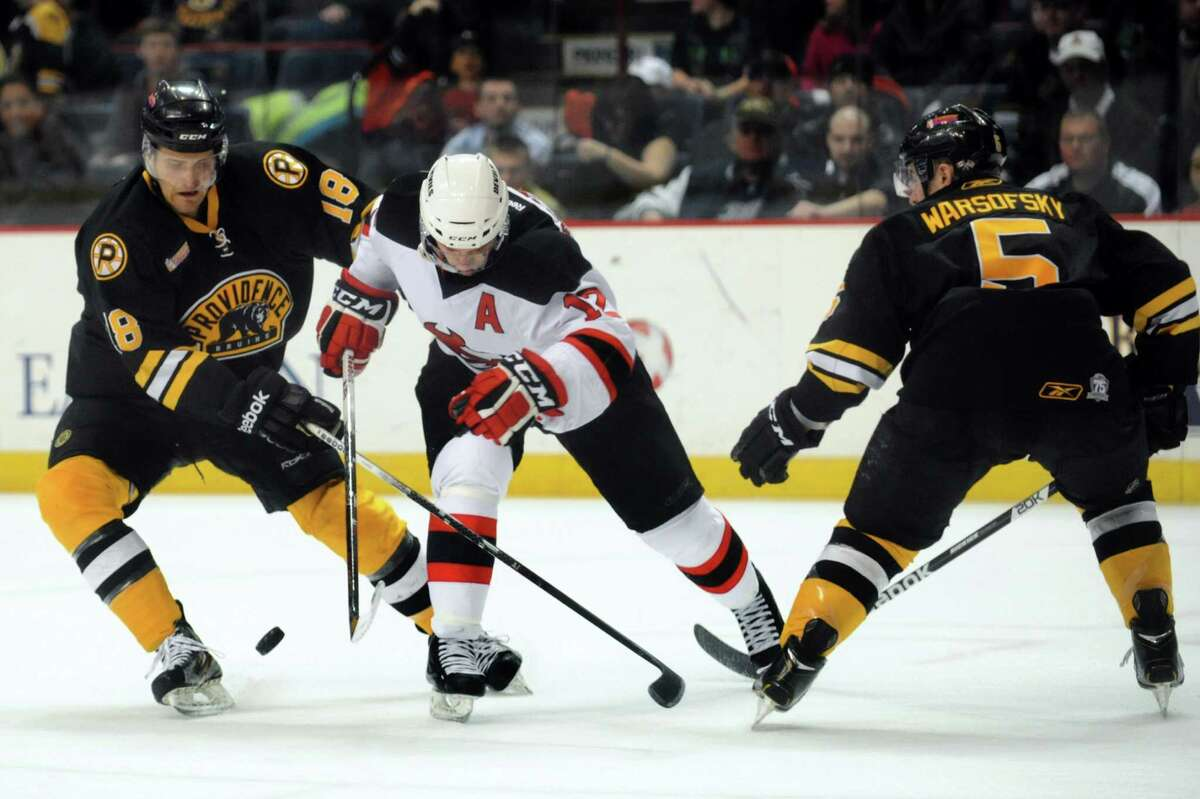 Devils' Tim Sestito, center, struggles for the puck with Bruins' Justin Florek, left, and David Warsofsky during their hockey game on Friday, April 5, 2013, at Times Union Center in Albany, N.Y. (Cindy Schultz / Times Union) 18, 12, 5