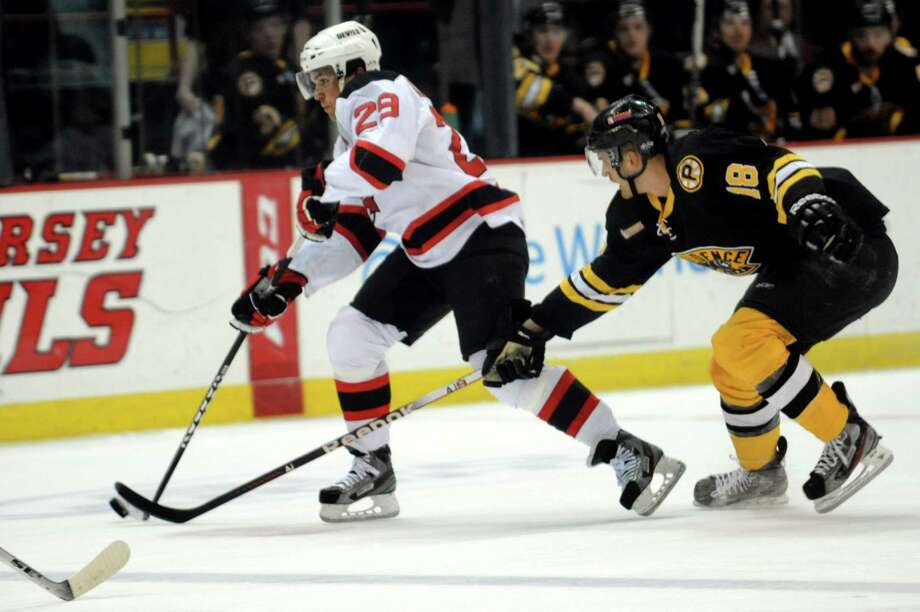 Devils' Matt Anderson, left, controls the puck as Bruins' Justin Florek defends during their hockey game on Friday, April 5, 2013, at Times Union Center in Albany, N.Y. (Cindy Schultz / Times Union)