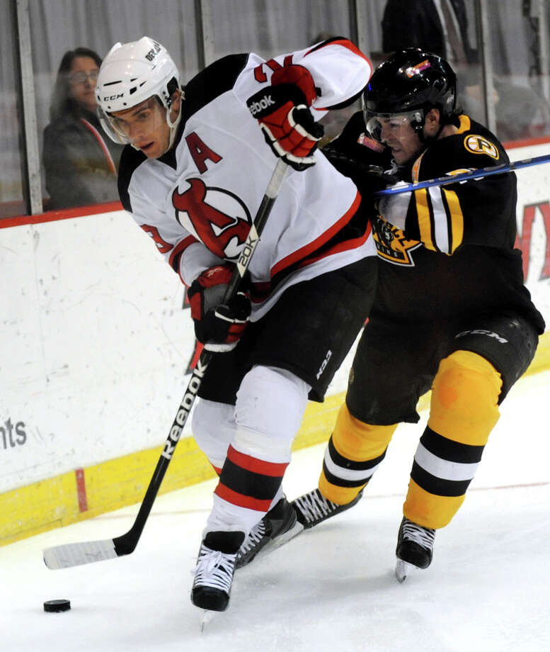 Devils' Matt Anderson, left, takes the puck behind the net as Bruins' Garnet Exelby defends during their hockey game on Friday, April 5, 2013, at Times Union Center in Albany, N.Y. (Cindy Schultz / Times Union)  18, 12, 5 Photo: Cindy Schultz /  00021748C