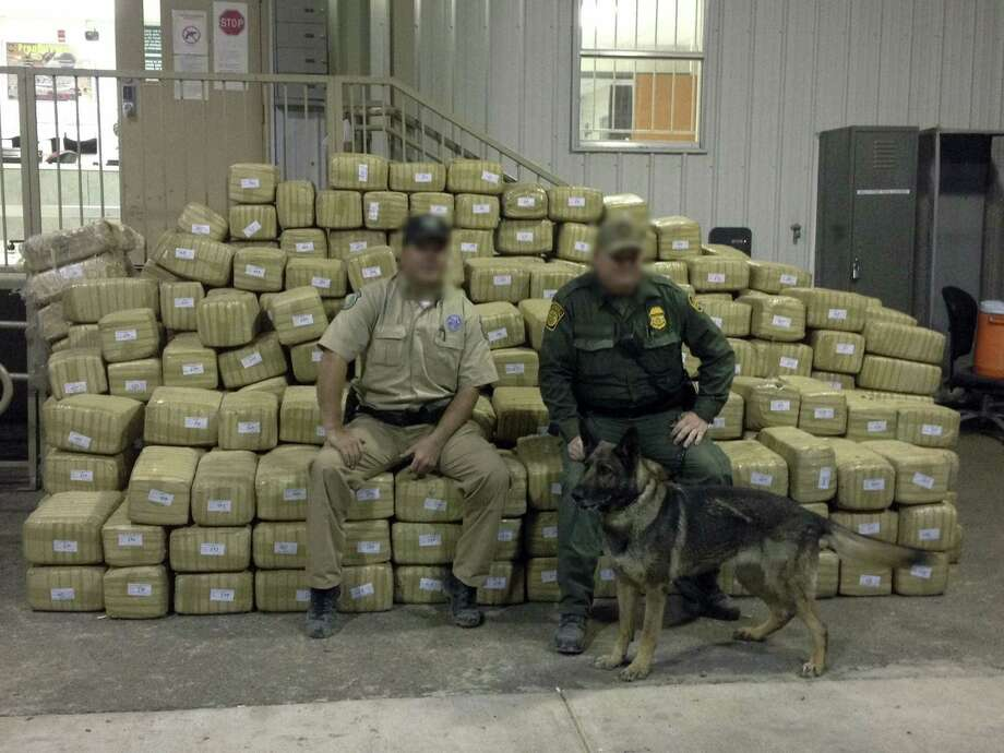 Game wardens, their faces obscured to protect their identities, display 2 tons of marijuana worth an estimated $4 million that was seized. Photo: Courtesy Photo