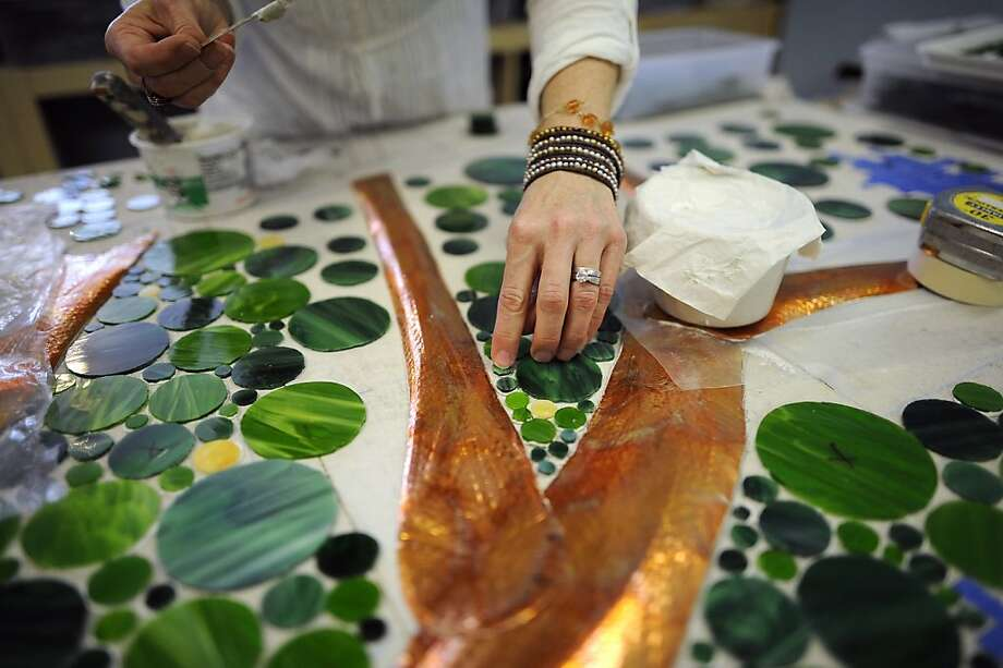 Gina Dominguez, owner of Snapshot Mosaics in Oakland, works on a wall piece for the Berkeley Public Library. Photo: Michael Short, Special To The Chronicle