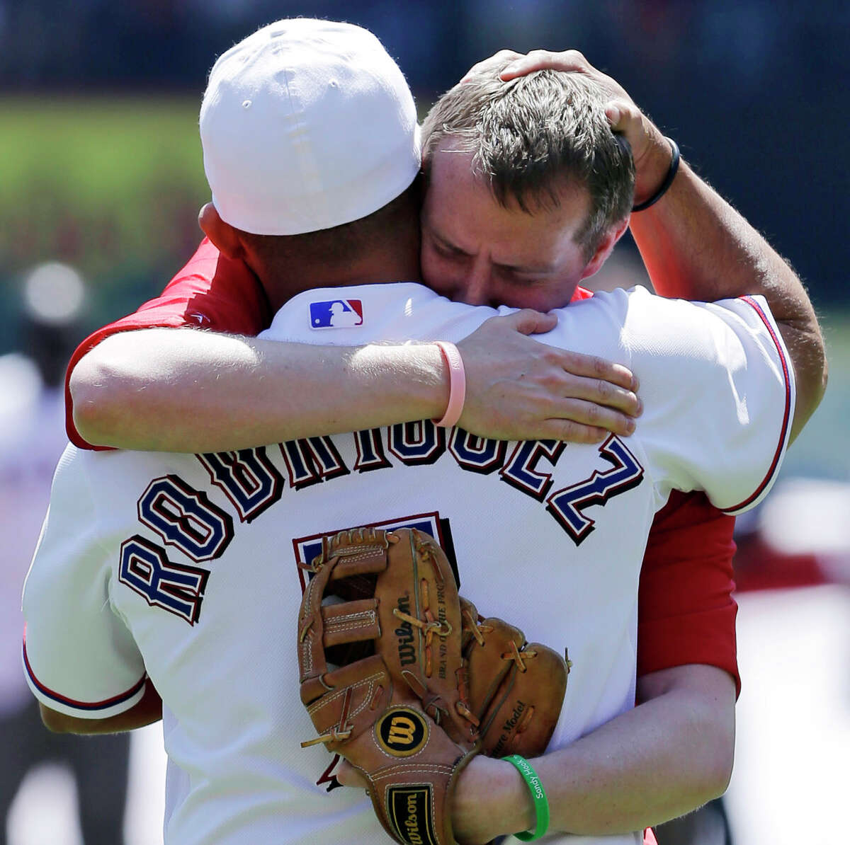 Robbie Parker, a North Texas native whose 6-year-old daughter, Emilie, was among the victims of the Sandy Hook school shooting, threw out a ceremonial first pitch to Rangers representative Ivan Rodriguez.
