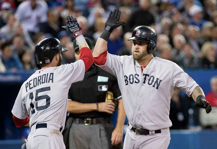 Boston Red Sox's Mike Napoli, right, celebrates his two-run home run with teammate Dustin Pedroia, left, while playing against the Toronto Blue Jays during fifth-inning baseball game action in Toronto, Friday, April 5, 2013. (AP Photo/The Canadian Press, Nathan Denette) Photo: Nathan Denette