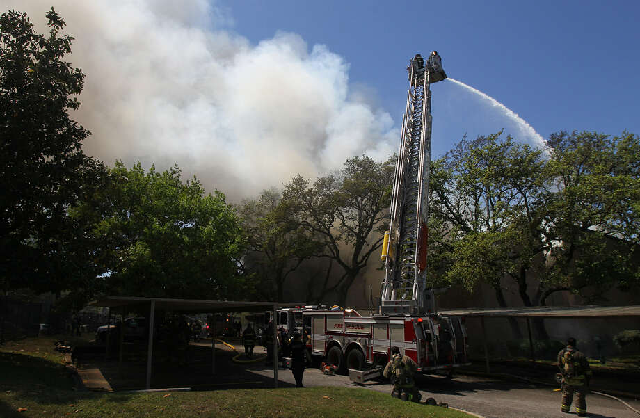 Firemen keep water on the hot spots Friday, a day after the blaze at the Castlewood Condominiums on Medical Drive. Photo: John Davenport / San Antonio Express-News