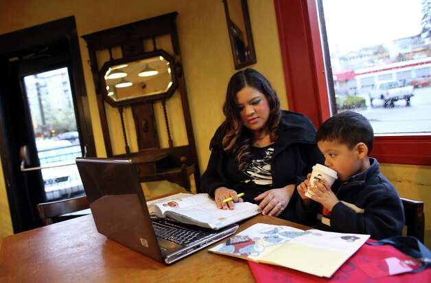 Xochitl Rojas, who came to the US from Mexico when she was three years-old, studies anatomy and physiology —part of the coursework for a nursing degree— at Uptown Espresso in West Seattle while her son Ezequiel, 4, sips a hot chocolate. Rojas works while in school and her husband works two jobs to help finance her education as she is not eligibile for state education aid.