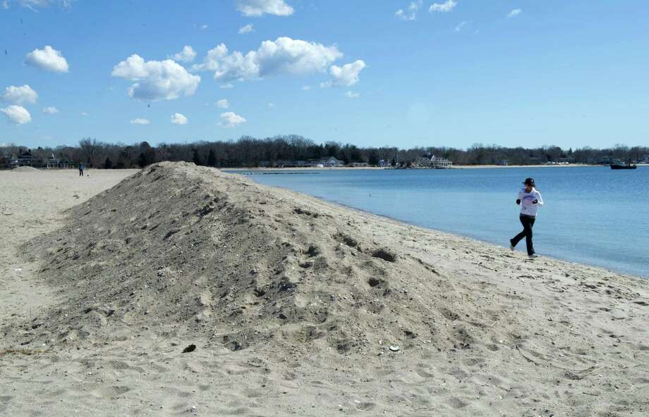 Jane Gjuraj runs past sand piled on the beach at Cove Island Park on Wednesday, March 27, 2013. Photo: Lindsay Perry / Stamford Advocate