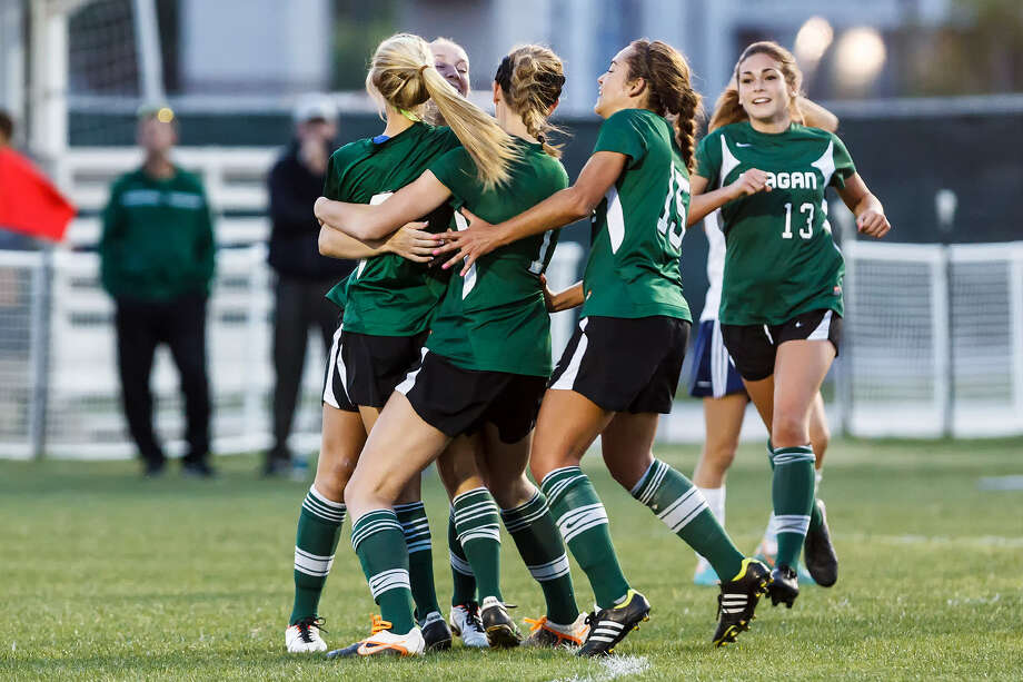 The Reagan Lady Rattlers rush to congratulate Lauren Bartels (left) after her goal in the first overtime period giving them what would prove to be the winning goal during their 2-1 overtime victory. Photo: Marvin Pfeiffer / San Antonio Express-News