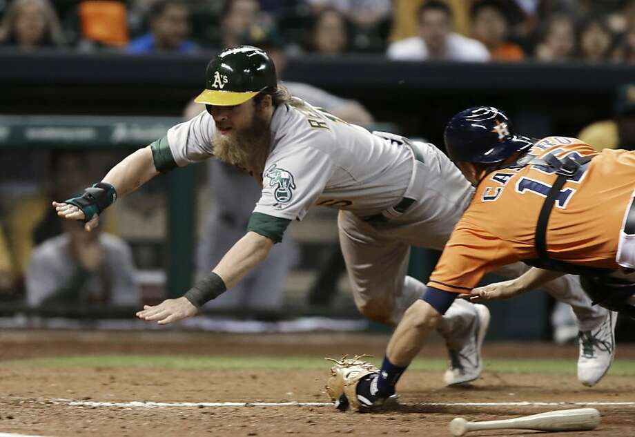 Oakland Athletics' Josh Reddick, left, dives to home plate to score on a John Jaso sacrifice bunt as Houston Astros catcher Jason Castro reaches for him in the fifth inning of a baseball game Friday, April 5, 2013, in Houston. (AP Photo/Pat Sullivan) Photo: Pat Sullivan, Associated Press