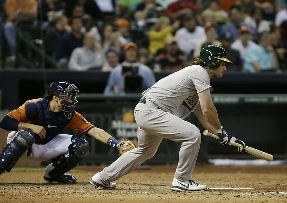 Oakland Athletics' John Jaso, right, bunts to score Josh Reddick as Houston Astros catcher Jason Castro reaches for the catch in the fifth inning of a baseball game Friday, April 5, 2013, in Houston. (AP Photo/Pat Sullivan) Photo: Pat Sullivan, Associated Press