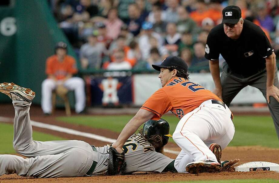 HOUSTON, TX - APRIL 05: Josh Reddick #16 of the Oakland Athletics slides safely back under the tag of Brett Wallace #29 of the Houston Astros at Minute Maid Park on April 5, 2013 in Houston, Texas. (Photo by Bob Levey/Getty Images) Photo: Bob Levey, Getty Images