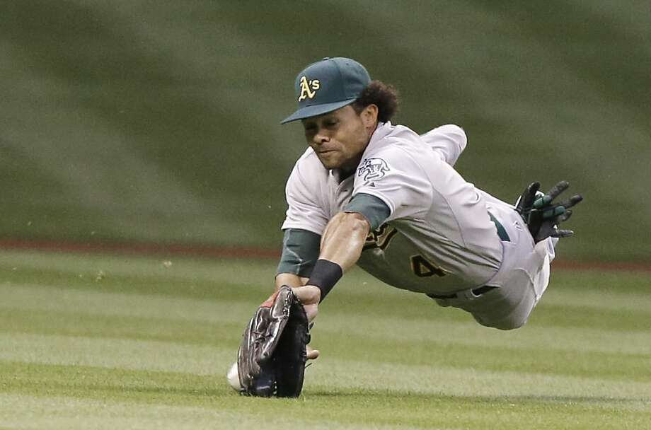 Oakland Athletics center fielder Coco Crisp dives for the ball and misses for a single for Houston Astros' Chris Carter in the first inning of a baseball game Friday, April 5, 2013, in Houston. (AP Photo/Pat Sullivan) Photo: Pat Sullivan, Associated Press