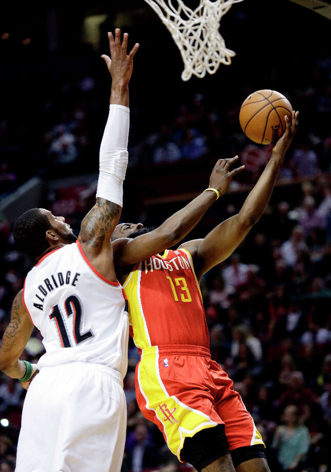 April 5: Rockets 116, Trail Blazers 98 Rockets guard James Harden drives to the basket against LaMarcus Aldridge of the Trail Blazers. Photo: Don Ryan
