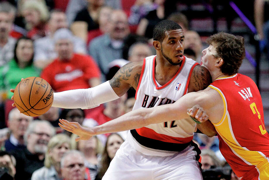 LaMarcus Aldridge of the Trail Blazers backs down Rockets center Omer Asik. Photo: Don Ryan