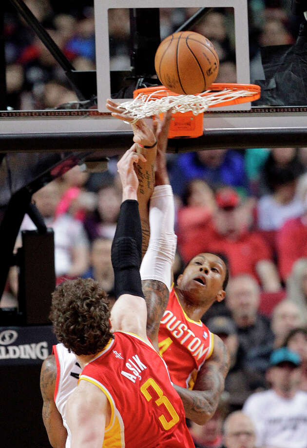 Trail Blazers forward LaMarcus Aldridge is defended by Omer Asik and Greg Smith of the Rockets. Photo: Don Ryan