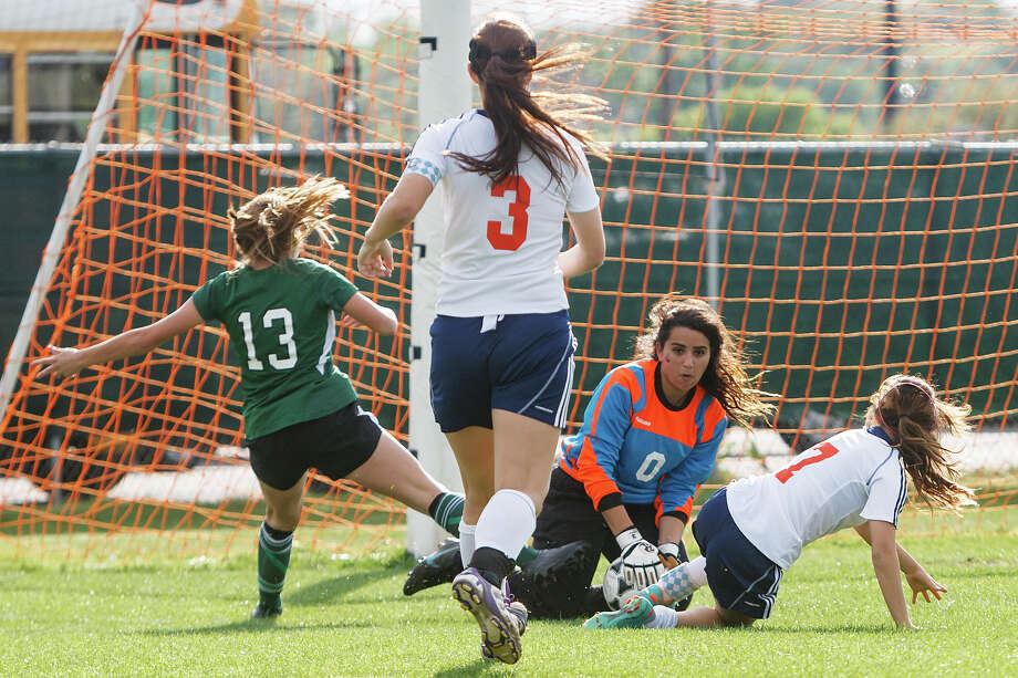 Brandeis goalie Ryzan Al-quarqaz (second from right) makes a save on a shot by Reagan's Sophia Acevedo (left) during the first half of their Class 5A second round playoff game. Photo: MARVIN PFEIFFER, Marvin Pfeiffer / Prime Time New / Prime Time Newspapers 2013