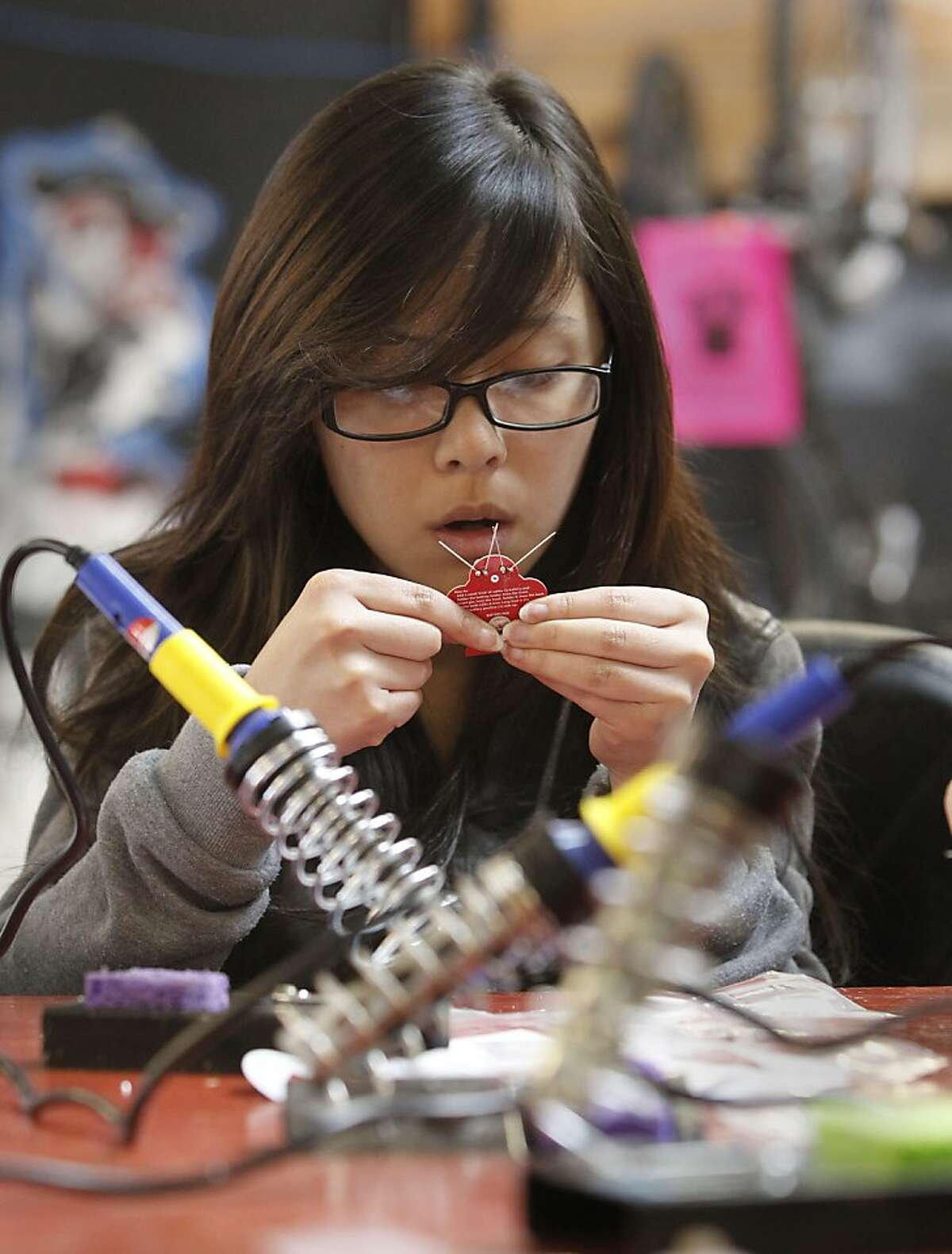 Gloria Chan, works on her flashing LED light project as students from Burton High School get a hands on experience in electronics and physics at Noisebridge, in San Francisco, Ca. on Tuesday April 2, 2013, as they learn about Noisebridge is an infrastructure provider for technical-creative projects, collaboratively run by its members as a non-profit educational corporation for public benefit.