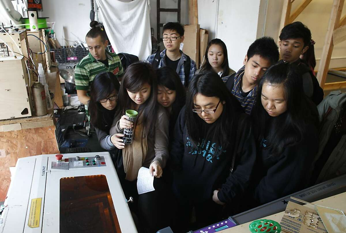Volunteer teacher, Jarrod Hicks, (left) shows students, (front l to r) Gloria Chang, Janet Huang, Tina Diep, Quincy Zhu and Stephanie Sun, (back l to r) Zhen Liu, Lilian Li, A.J. Lenon and Russel Gonzales, the results of a computer aided laser cutting design he demonstrated for the students from Burton High School as they get a first hand experience at Noisebridge, in San Francisco, Ca. on Tuesday April 2, 2013, as they learn about Noisebridge is an infrastructure provider for technical-creative projects, collaboratively run by its members as a non-profit educational corporation for public benefit.