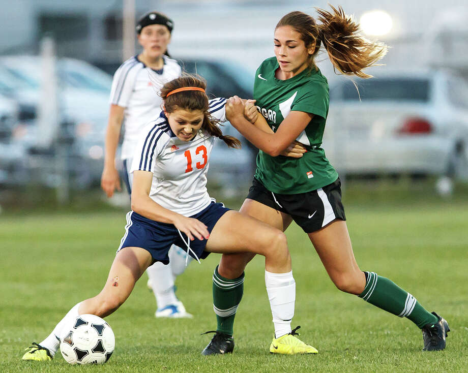 Brandeis's Kelsey Kohler (left) gets tied up with Reagan's Sophia Acevedo as they fight for the ball during the first overtime period in their Class 5A second round playoff game. Photo: MARVIN PFEIFFER, Marvin Pfeiffer / Prime Time New / Prime Time Newspapers 2013