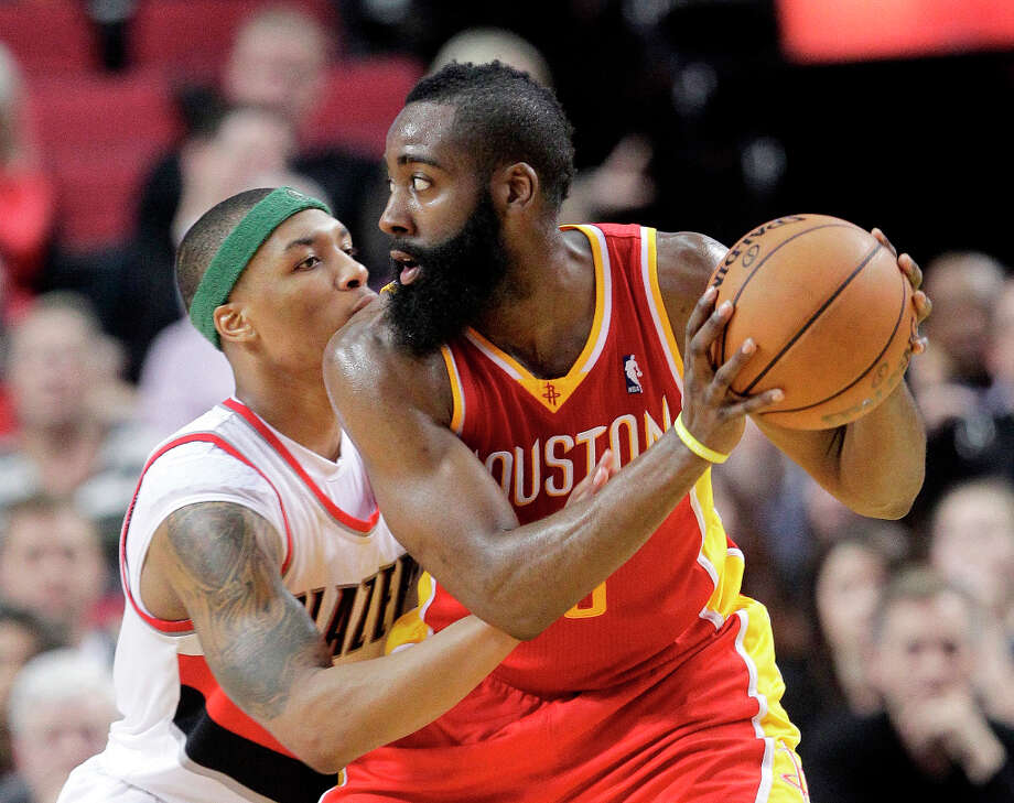 Rockets guard James Harden looks to make a move on Trail Blazers point guard Damian Lillard. Photo: Don Ryan