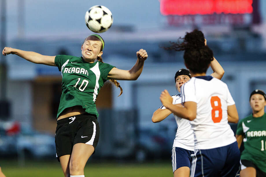 Reagan's Carly Hankins (left) heads the ball during the second overtime period in their Class 5A second round playoff game. Photo: MARVIN PFEIFFER, Marvin Pfeiffer / Prime Time New / Prime Time Newspapers 2013