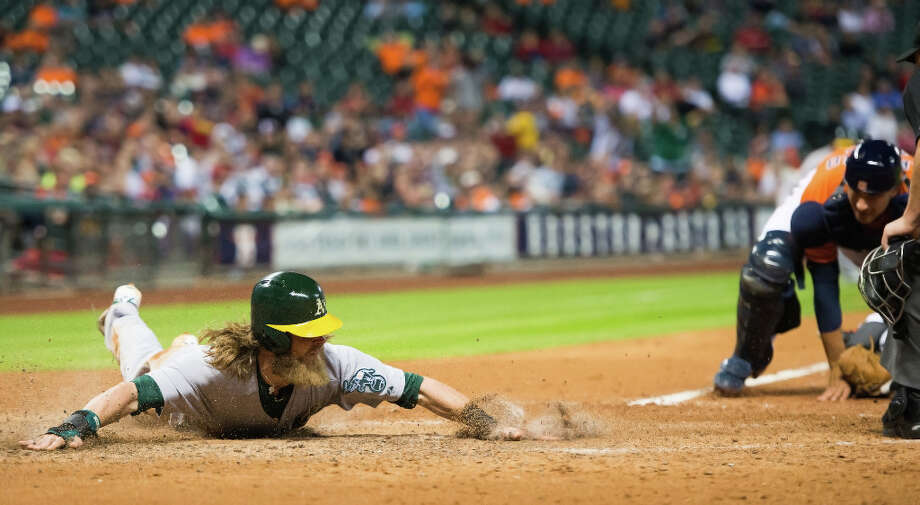 April 5: Athletics 8, Astros 3Oakland right fielder Josh Reddick slides home with a run as Astros catcher Jason Castro can't make a tag as the A's score  seven runs in the top of the fifth. Photo: Smiley N. Pool, Houston Chronicle / © 2013  Smiley N. Pool