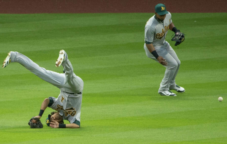 Athletics center fielder Coco Crisp tumbles upside-down as he tries to dive for a single by Astros' Chris Carter in the first inning. Photo: Smiley N. Pool, Houston Chronicle / © 2013  Smiley N. Pool