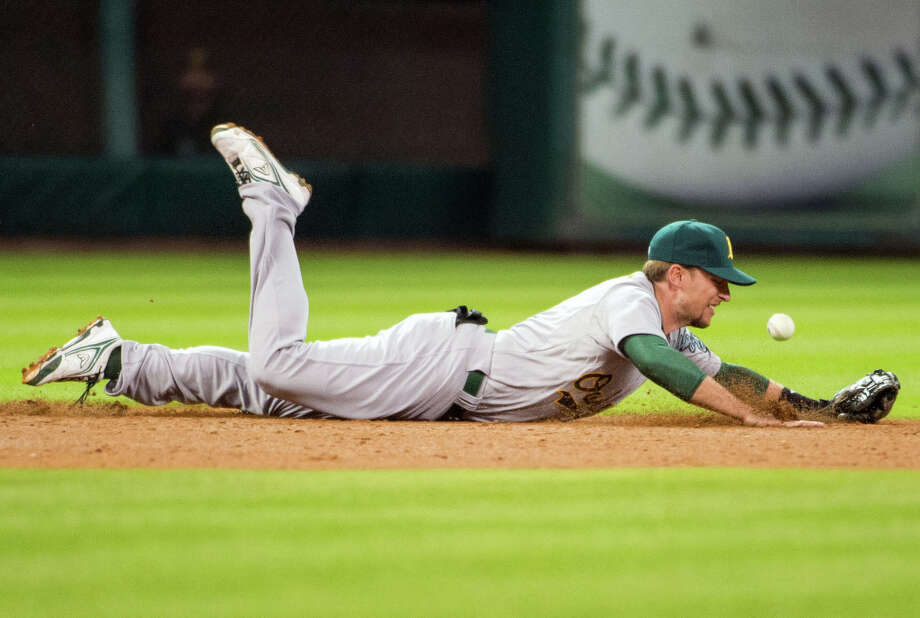 Athletics shortstop Jed Lowrie dives but can't make the play on a single by Astros second baseman Jose Altuve. Photo: Smiley N. Pool, Houston Chronicle / © 2013  Smiley N. Pool