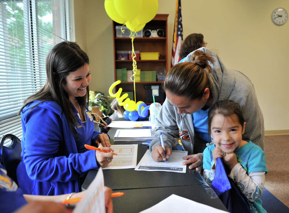 Anahi Rodriguez, 4, is all smiles as her mother, Veronica Rodriguez, fills out paperwork after winning one of 112 openings in the IDEA Carver school kindergarten class on Saturday morning, April 6, 2013. IDEA Carver teacher Anna Linda Ochoa looks on. Photo: Robin Jerstad, San Antonio Express-News