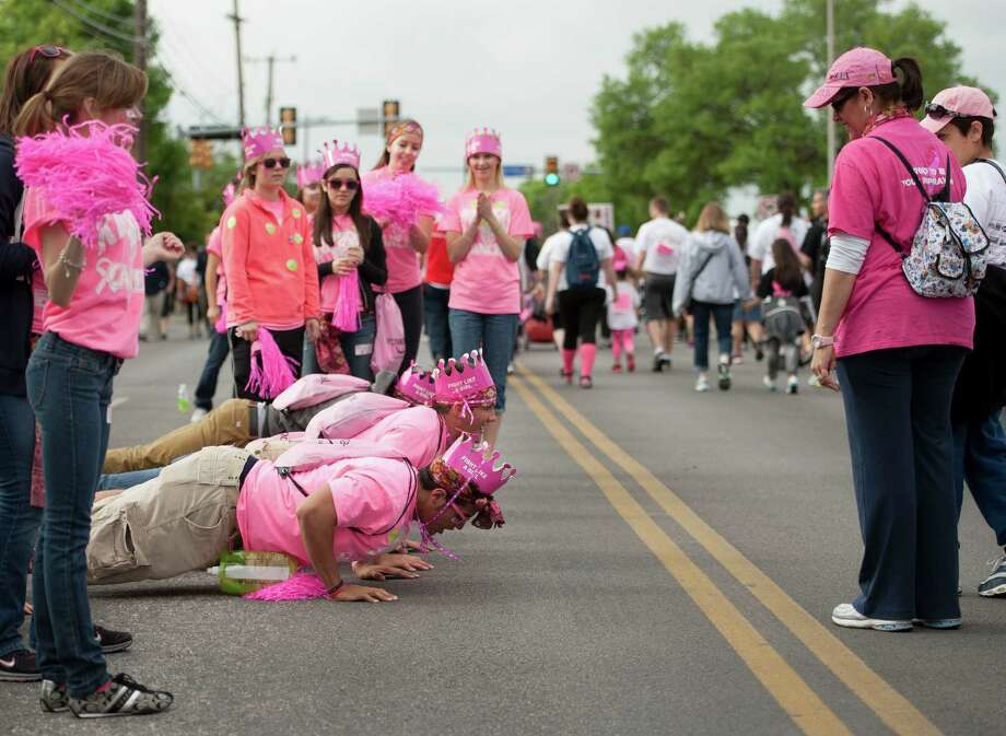 Students from the Madison High School PALS program do push-ups in honor of cancer survivors during the Susan G. Komen Race for the Cure, Saturday, April 6, 2013, in San Antonio. (Darren Abate/For the Express-News) Photo: Darren Abate, Darren Abate/Express-News