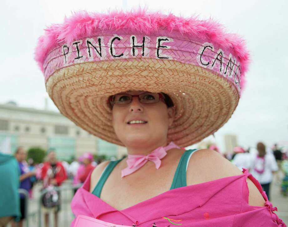 "Wearing a sombrero that reads, ""Pinche Cancer,"" Cynthia Garza prepares to participate in the Susan G. Komen Race for the Cure, Saturday, April 6, 2013, in San Antonio. (Darren Abate/For the Express-News) Photo: Darren Abate, Darren Abate/Express-News"