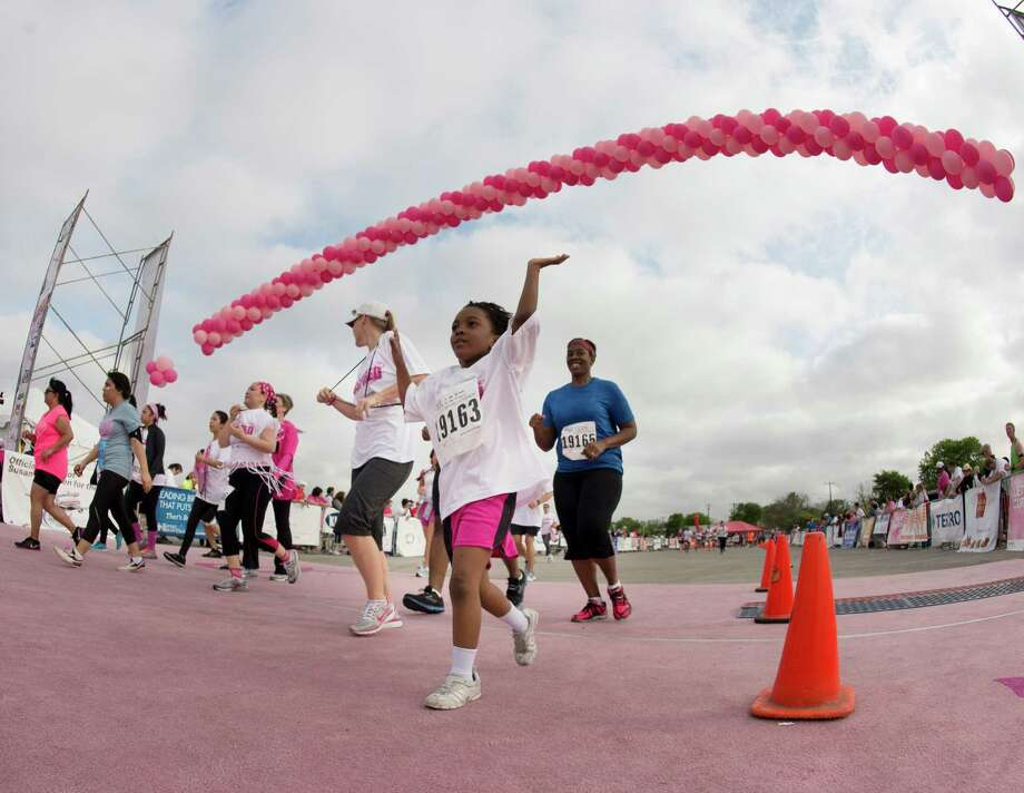 Participants cross the finish line during the Susan G. Komen Race for the Cure, Saturday, April 6, 2013, in San Antonio. (Darren Abate/For the Express-News) Photo: Darren Abate, Darren Abate/Express-News